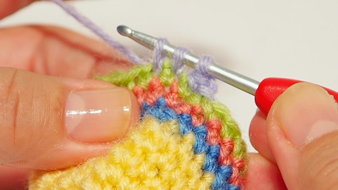 There are 3 loops on the crochet hook. Wrap the wool round the crochet hook and pull through the 3 loops.