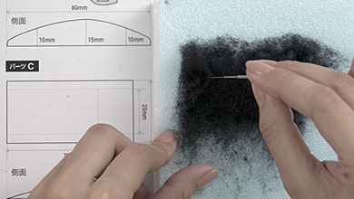 Tear off a piece of black sheet felt one size bigger than pattern C and form the shape while poking with a needle.